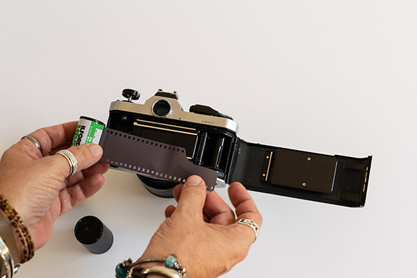 Insert end into sprocket - How To Load 35mm Film