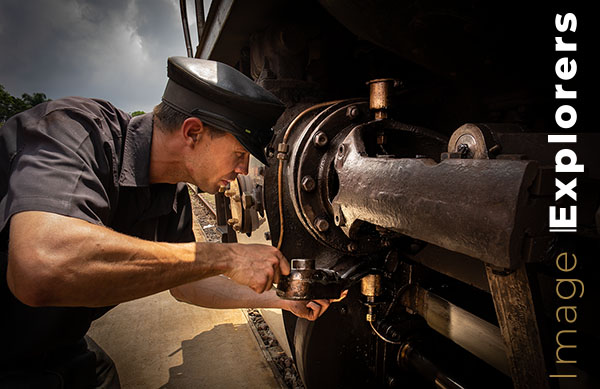 Driver oiling steam train after