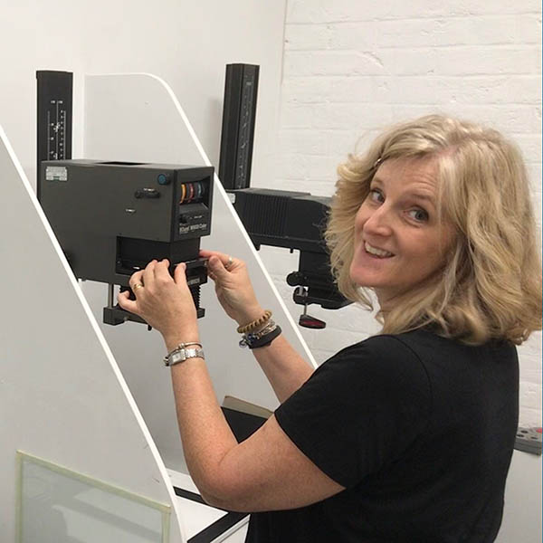Ally putting the negative into the enlarger showing how to do darkroom printing